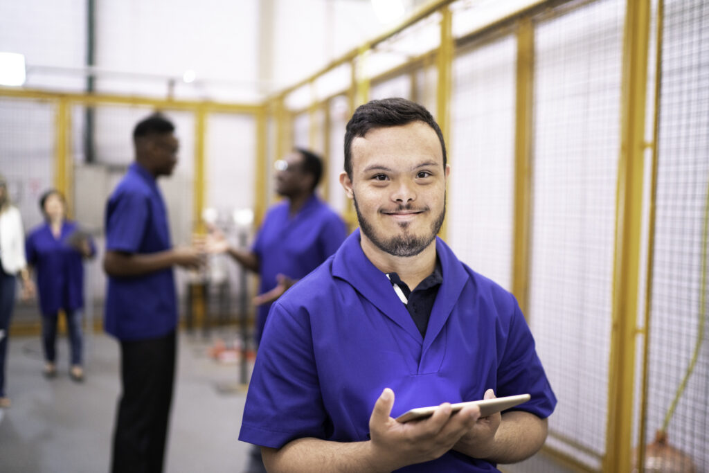 Portrait of special needs employee holding digital tablet in industry setting